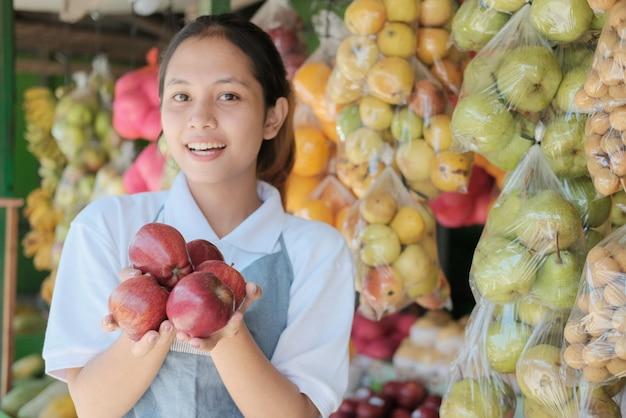 Uśmiechnięty azjatycki sprzedawca pani niosący świeże czerwone jabłka na tle stoiska ze świeżymi owocami