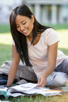 Uśmiechnięty azjatykci kobieta uczeń studiuje outdoors