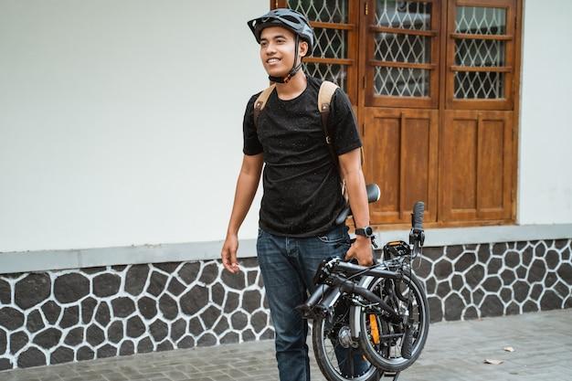 Uśmiechnięty azjatykci młody człowiek niesie jej falcowanie rower