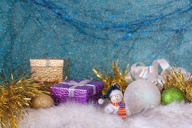 Uśmiechnięty bałwan na białym futerku obok bombek i pudełek na prezenty. niebieskie tło z efektem padającego śniegu. selektywne skupienie się na bałwanie.