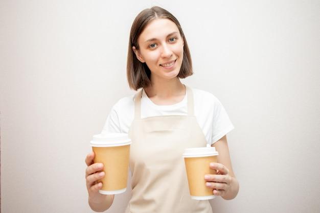 Uśmiechnięty barista w fartuchu, trzymając dwa kubki z brązowego papieru. kobieta w fartuchu patrząc na kamery i uśmiechnięty.