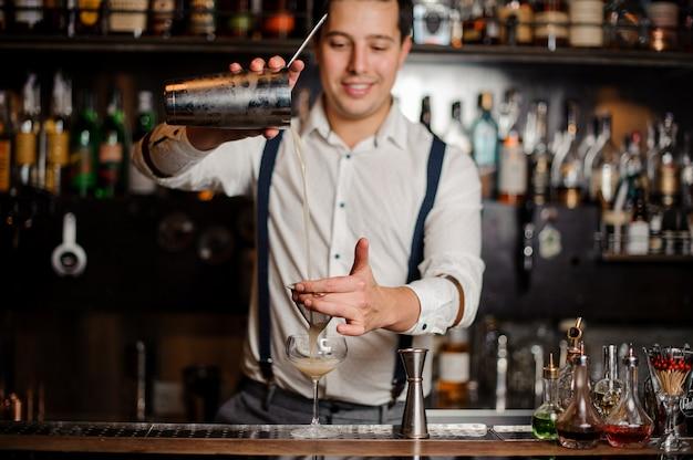 Uśmiechnięty barman robi koktajl przy stojaku barowym