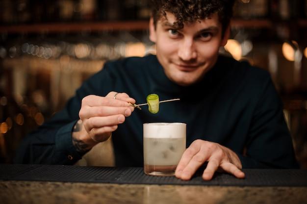 Uśmiechnięty barman serwujący koktajl z ogórkiem w barze licznika
