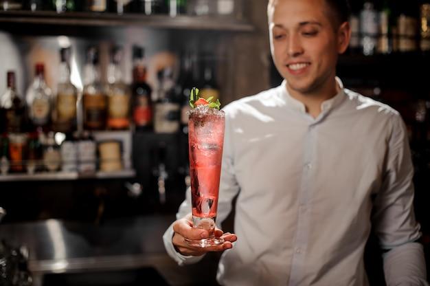 Uśmiechnięty barman trzyma przejrzystego czerwonego koktajl w szkle na kontuarze
