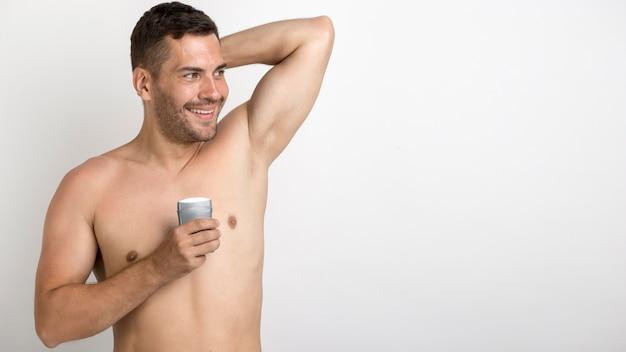 Uśmiechnięty bez koszuli powabny mężczyzna mienia rolka na dezodorancie stoi przeciw białemu tłu