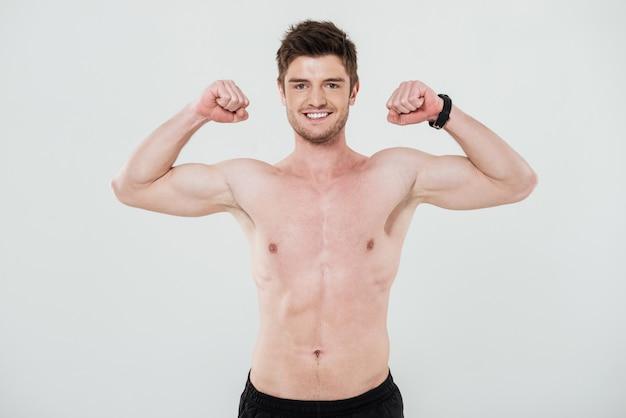 Uśmiechnięty bez koszuli sportowiec pokazuje bicepsy i patrzeje kamerę