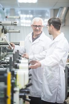 Uśmiechnięty białowłosy pracownik w fartuchu laboratoryjnym za pomocą tabletu podczas analizy wydajności prasy drukarskiej z kolegą w sklepie fabrycznym