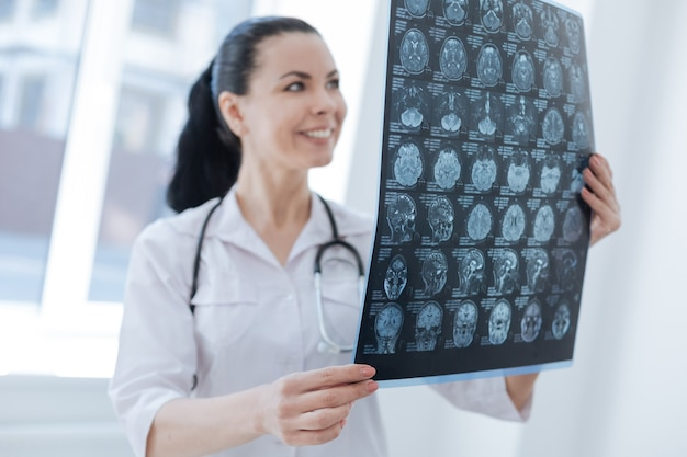 Uśmiechnięty biegły dojrzały radiolog pracujący w klinice podczas badania rentgenowskiego mózgu i wykrywania guza