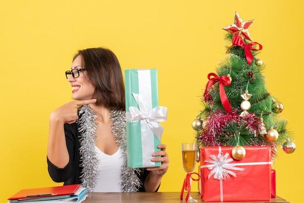 Uśmiechnięty biznes dama w garniturze z okularami wskazując jej prezent i siedząc przy stole z drzewem xsmas na nim w biurze