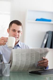 Uśmiechnięty biznesmen czyta gazetę i ma kawę