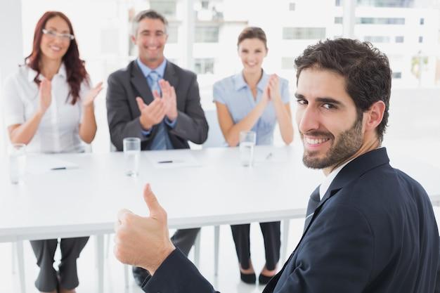 Uśmiechnięty biznesmen daje aprobatom z pracownikami