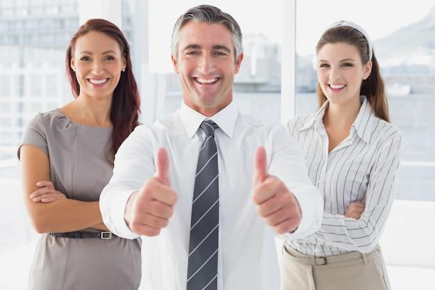 Uśmiechnięty biznesmen daje aprobatom