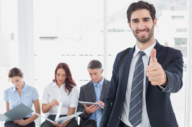 Uśmiechnięty biznesmen i jego współpracownicy