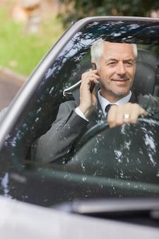 Uśmiechnięty biznesmen jedzie drogiego kabriolet na telefonie