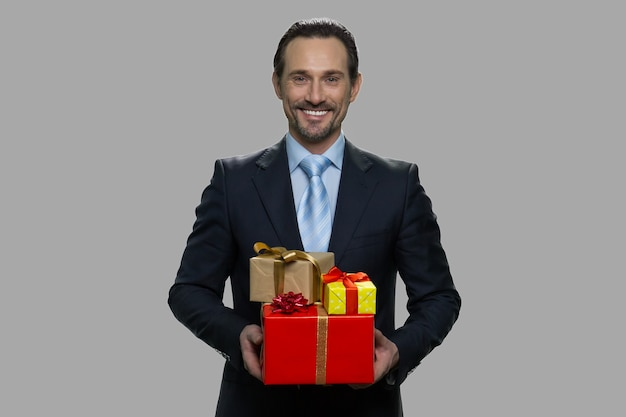 Uśmiechnięty biznesmen kaukaski gospodarstwa pudełka. portret przystojny mężczyzna w garniturze posiadający wiele pudełek na prezent. świąteczny sezon świąteczny.