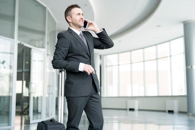Uśmiechnięty biznesmen mówiąc przez telefon na lotnisku