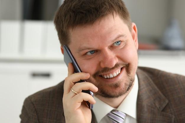 Uśmiechnięty biznesmen opowiada na telefonie komórkowym