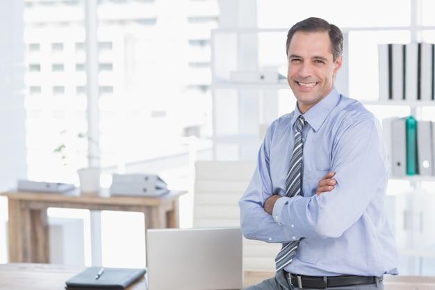 Uśmiechnięty biznesmen patrzeje kamerę