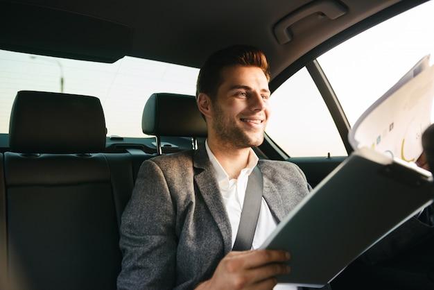 Uśmiechnięty biznesmen patrzeje przez dokumentów