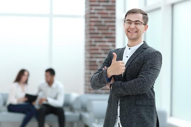 Uśmiechnięty biznesmen pokazuje kciuk up. koncepcja sukcesu