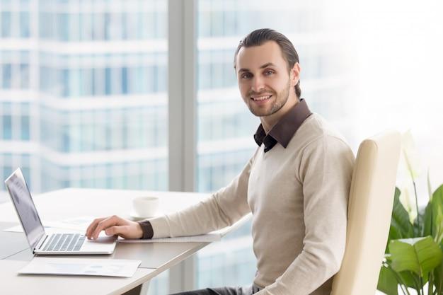 Uśmiechnięty biznesmen pracuje przy biurem, patrzeje kamerę, używać laptop