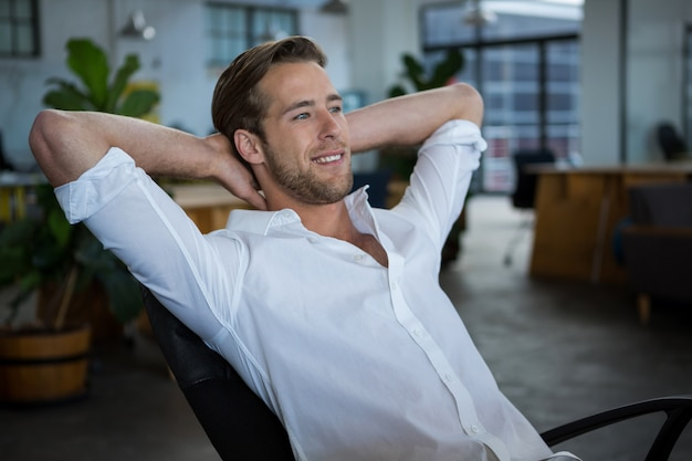 Uśmiechnięty biznesmen relaksuje na krześle