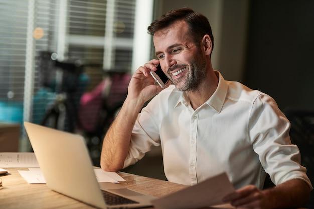 Uśmiechnięty biznesmen rozmawia przez telefon komórkowy