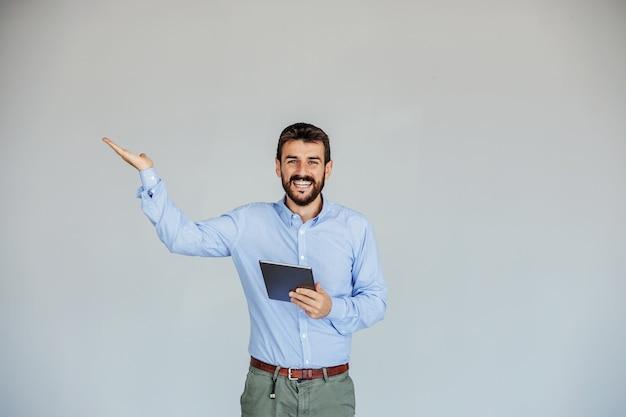Uśmiechnięty biznesmen stojący, trzymając tablet i trzymając rękę, jakby coś pokazywał.