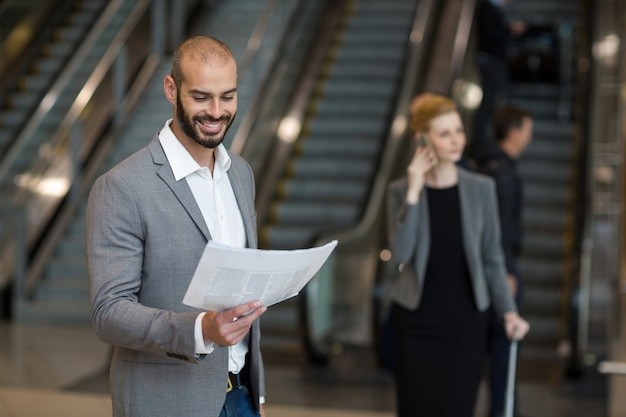 Uśmiechnięty biznesmen stojący w poczekalni czytania gazety