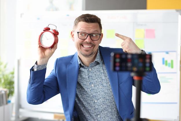 Uśmiechnięty biznesmen trzyma czerwony budzik i prowadzi internetowe kursy zarządzania czasem