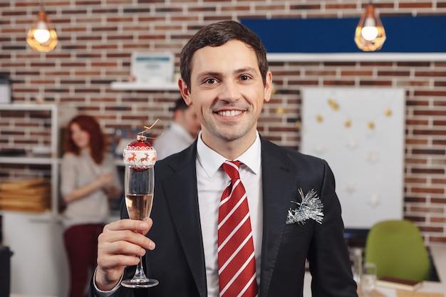 Uśmiechnięty biznesmen trzyma szkło z szampanem