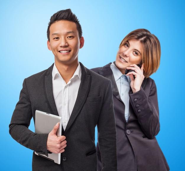 Uśmiechnięty biznesmen trzymając tabletkę obok swojego partnera