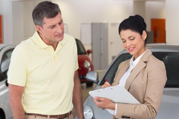 Uśmiechnięty biznesmen undersign kontrakt samochodowy