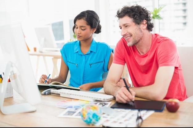 Uśmiechnięty biznesmen używa laptop i digitizer