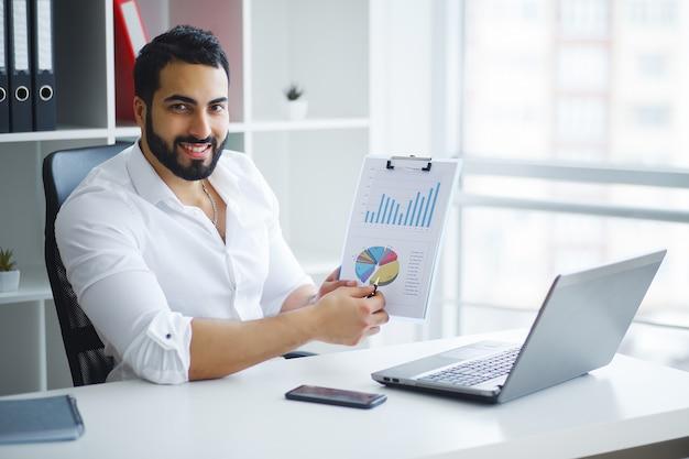 Uśmiechnięty biznesmen używa laptop przy biurkiem w biurze