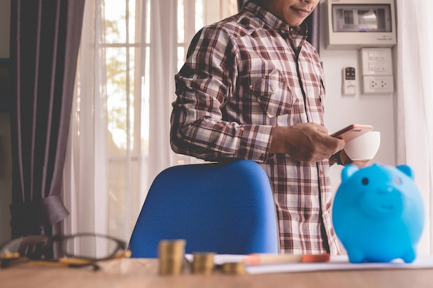 Uśmiechnięty biznesmen używa telefon w biurowym pokoju.