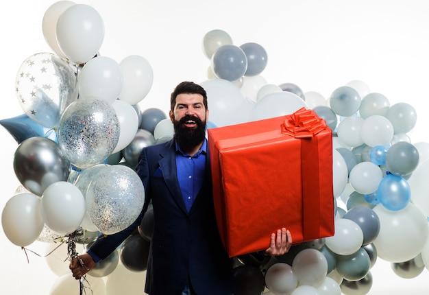 Uśmiechnięty biznesmen z balonami z helem i dużym teraźniejszości pudełkiem. brodaty mężczyzna z prezentem. urodziny, święta, uroczystości.