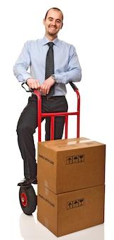 Uśmiechnięty biznesmen z czerwoną ciężarówką i pudełkami