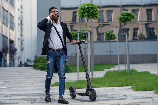 Uśmiechnięty biznesmen z elektrycznym skuterem w pobliżu nowoczesnego budynku biznesowego