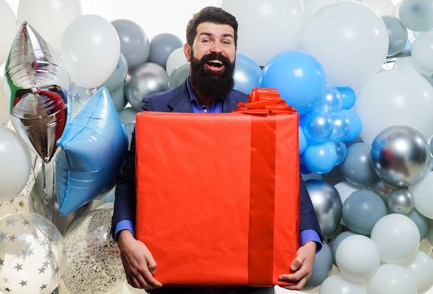 Uśmiechnięty biznesmen z helem balony z dużą teraźniejszością. świętowanie urodzin. szczęśliwy brodaty mężczyzna z pudełko.