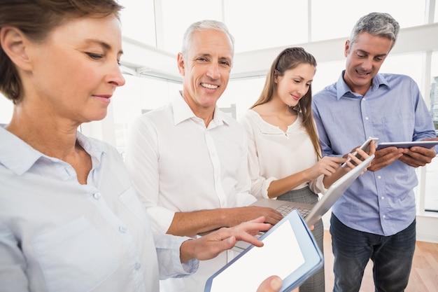 Uśmiechnięty biznesmen z laptopem obok kolegów