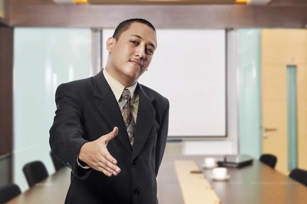 Uśmiechnięty biznesmen z otwartą ręką przygotowywającą wręczać potrząśnięcie