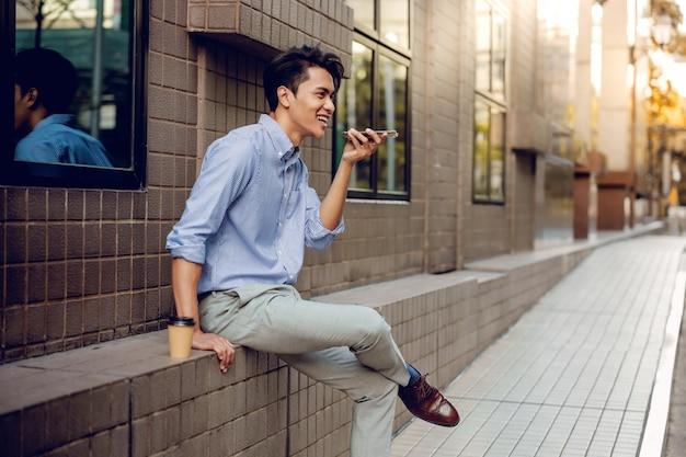 Uśmiechnięty biznesmen za pomocą sterowania głosowego za pomocą smartfona. szczęśliwy młody człowiek trzyma telefon komórkowego w mieście