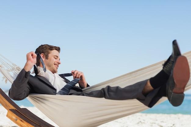 Uśmiechnięty biznesmena lying on the beach w hamock bierze daleko jego krawat