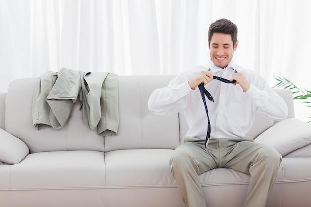 Uśmiechnięty biznesmena obsiadanie na kanapie rozluźnia jego krawat