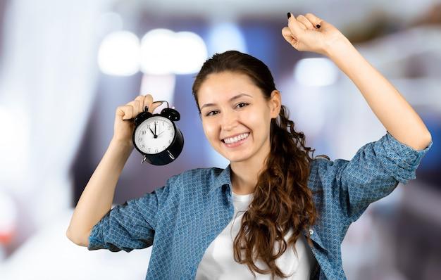 Uśmiechnięty biznesowej kobiety mienia budzik. na białym tle portret