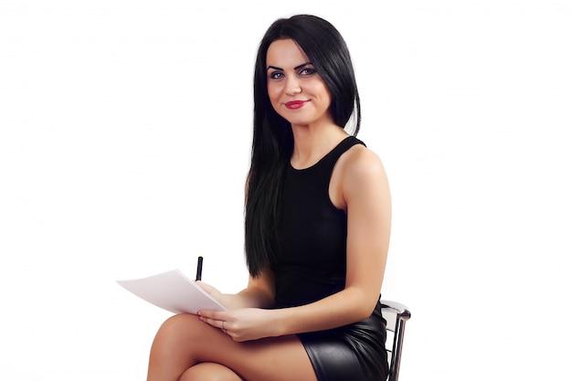 Uśmiechnięty biznesowej kobiety obsiadanie w krześle. młody biznesmena uśmiech, napisał w dokumencie, odizolowywającym