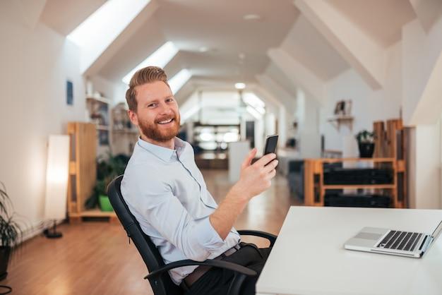 Uśmiechnięty biznesowy mężczyzna w jaskrawym biurze używać telefon.