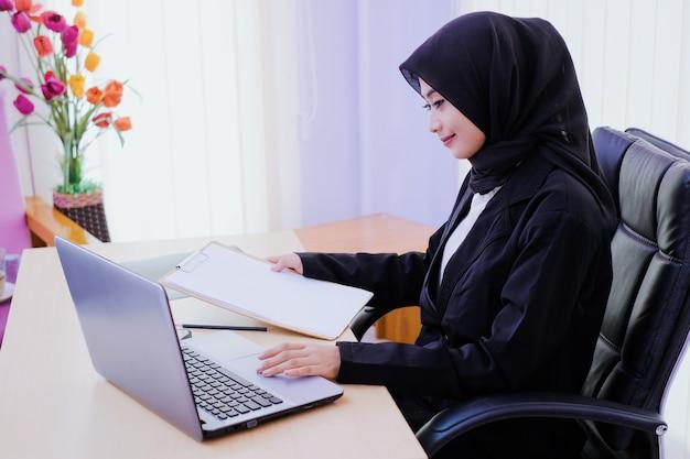 Uśmiechnięty bizneswoman analizuje dokument siedzi w biurze