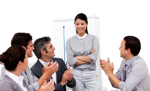 Uśmiechnięty bizneswoman brawo dla jej prezentaci